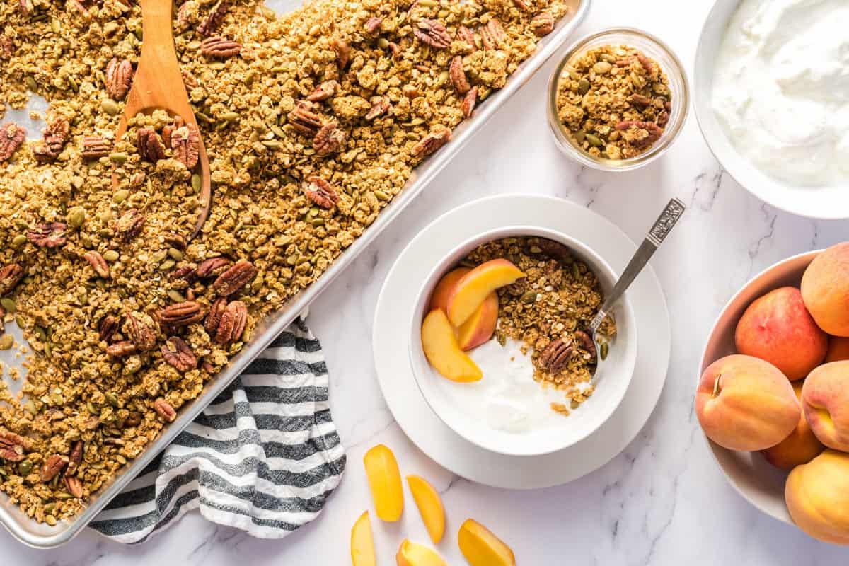 a sheet pan of pumpkin maple pecan granola beside a bowl with yogurt, granola, and peaches