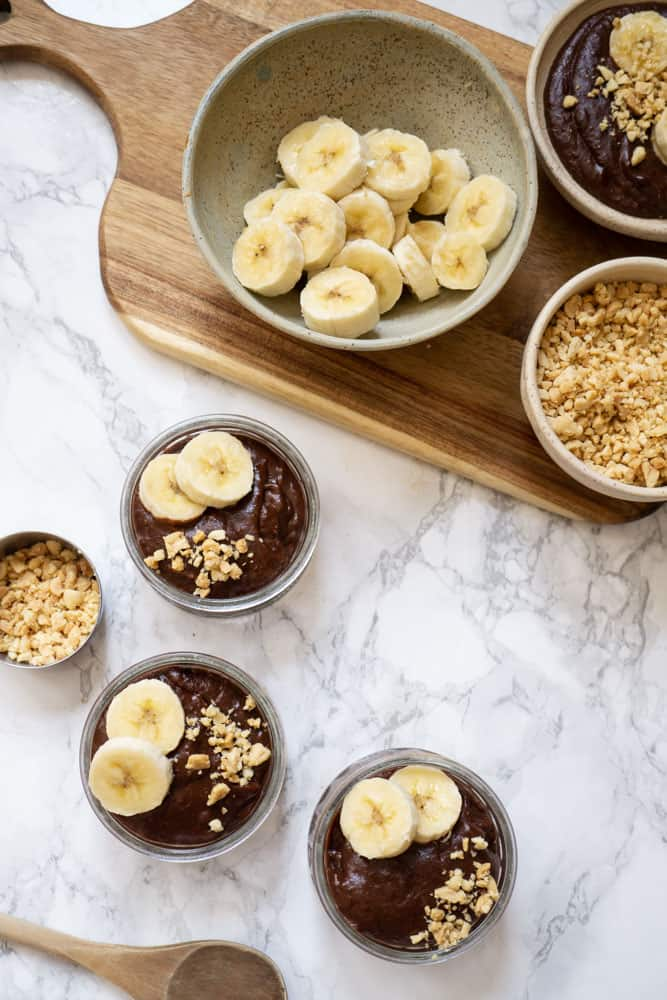 3 bowls of Chocolate Pudding with Peanut Butter topped with bananas and chopped peanuts