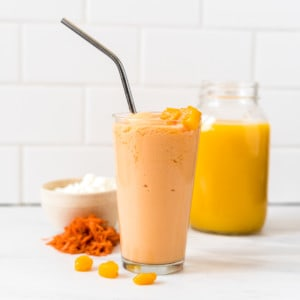 a glass of peaches n cream smoothie with orange juice, cottage cheese, carrots and peach slices surrounding it.