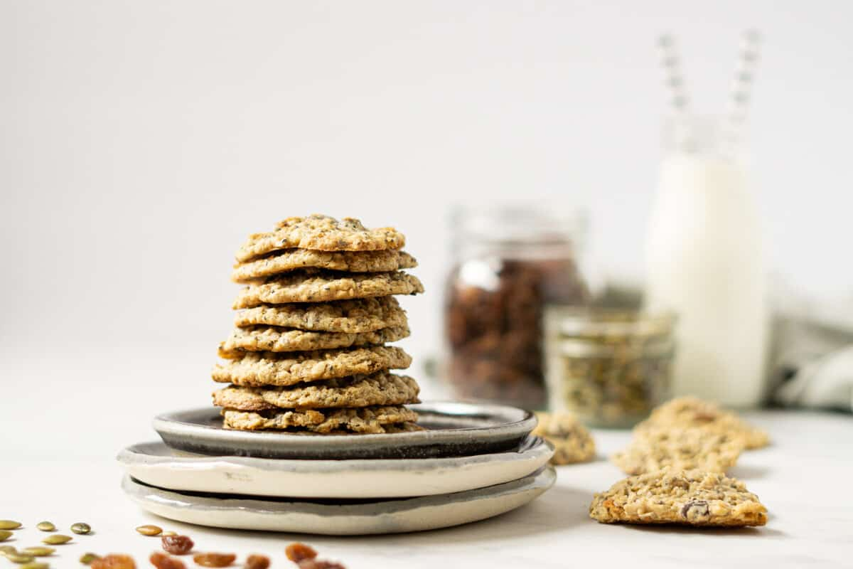 a plate of stacked trail mix cookies in front of a glass of milk and jars of raisins and pumpkin seeds