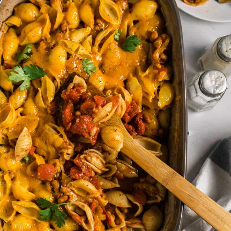 pasta casserole in 9x12 dish with some scooped out onto a plate