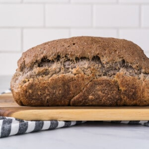 a side view of vegan sourdough bread on a wooden cutting board