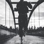 black-and-white-photo-of-woman-running-on-bridge-in-the-rain