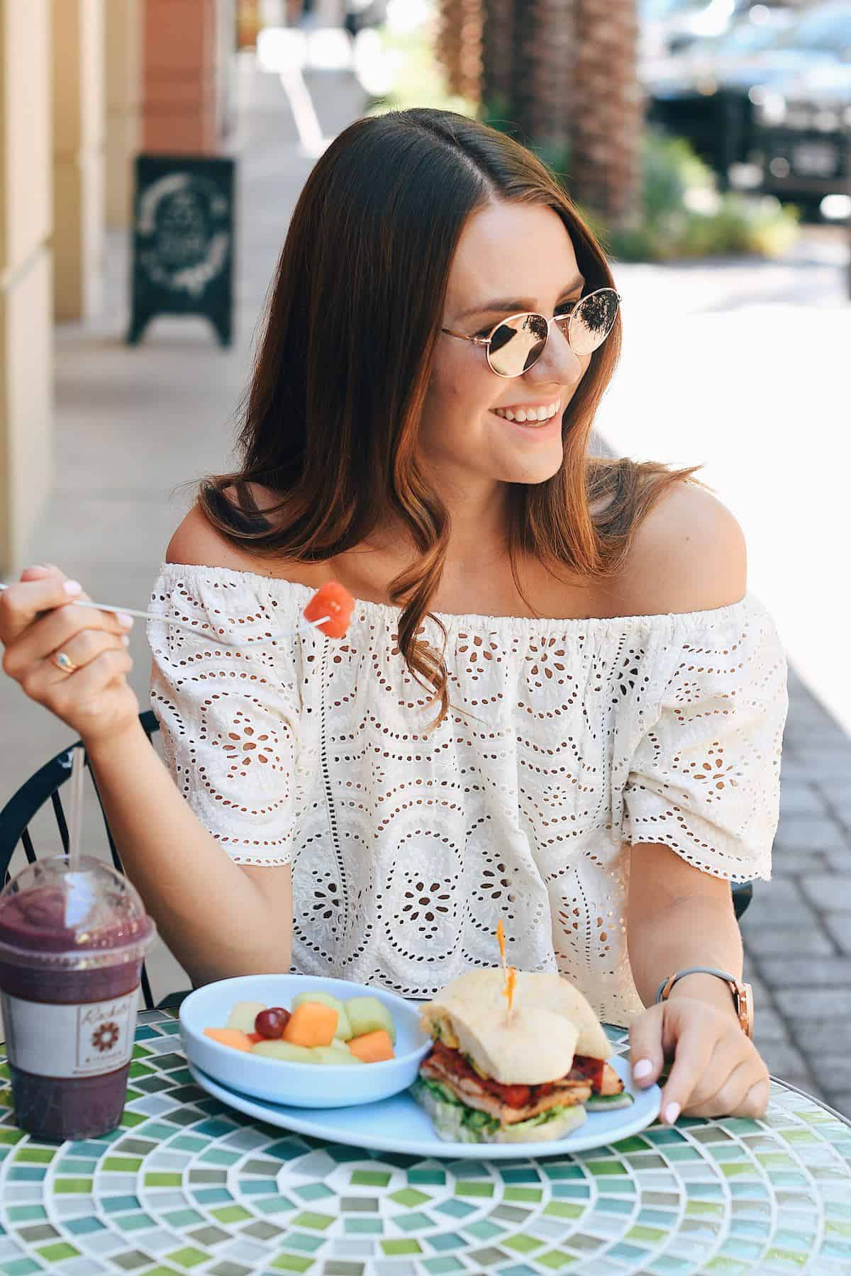 woman wearing sunglasses sitting at an outdoor cafe eating a fruit salad