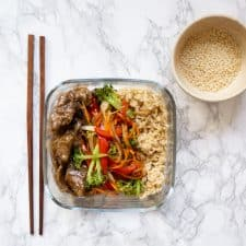 Ginger beef, veggies, brown rice in a meal prep container with toasted sesame seeds and chopsticks