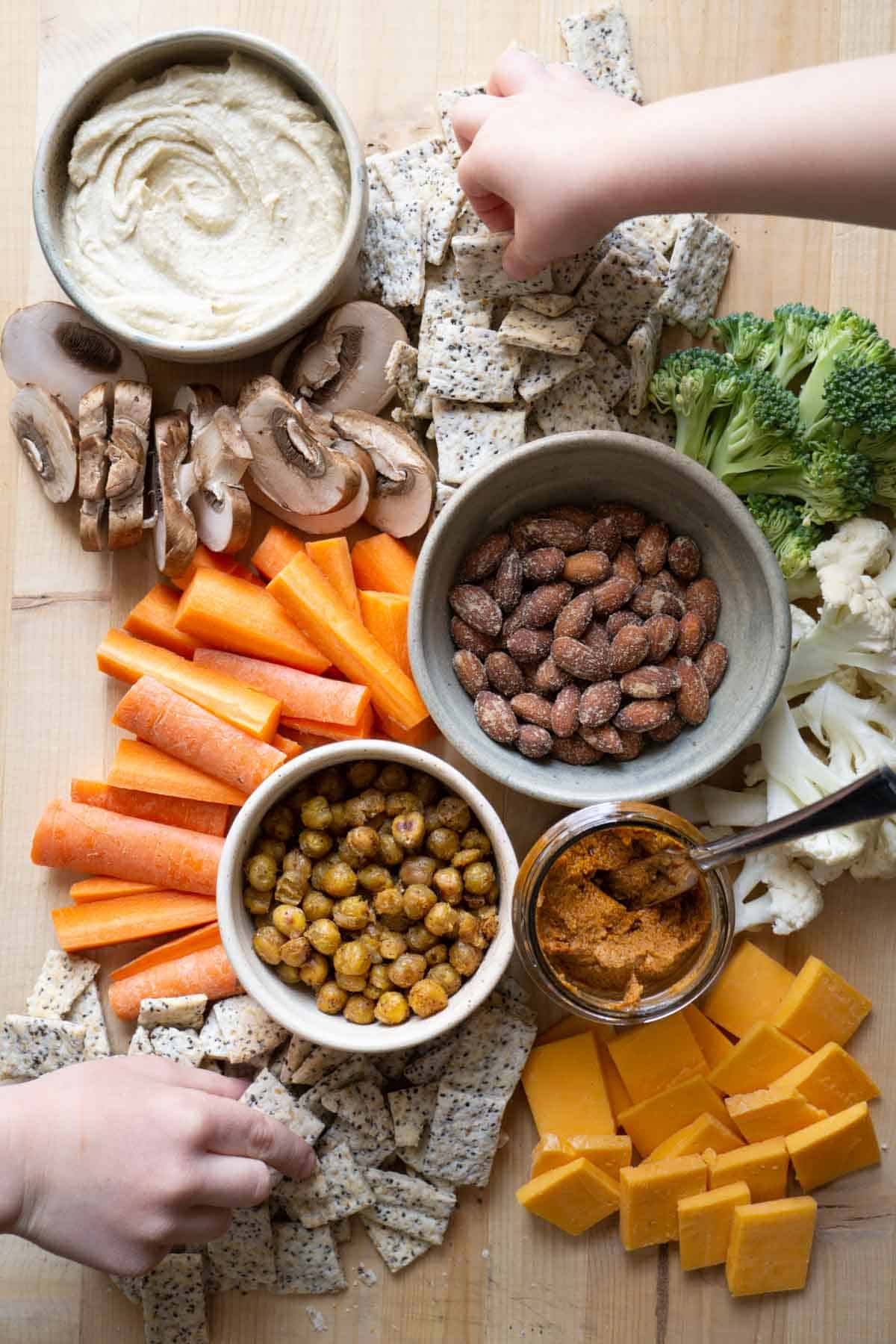 overview of snack board with hummus, sourdough crackers, veggies, nuts, and cheese