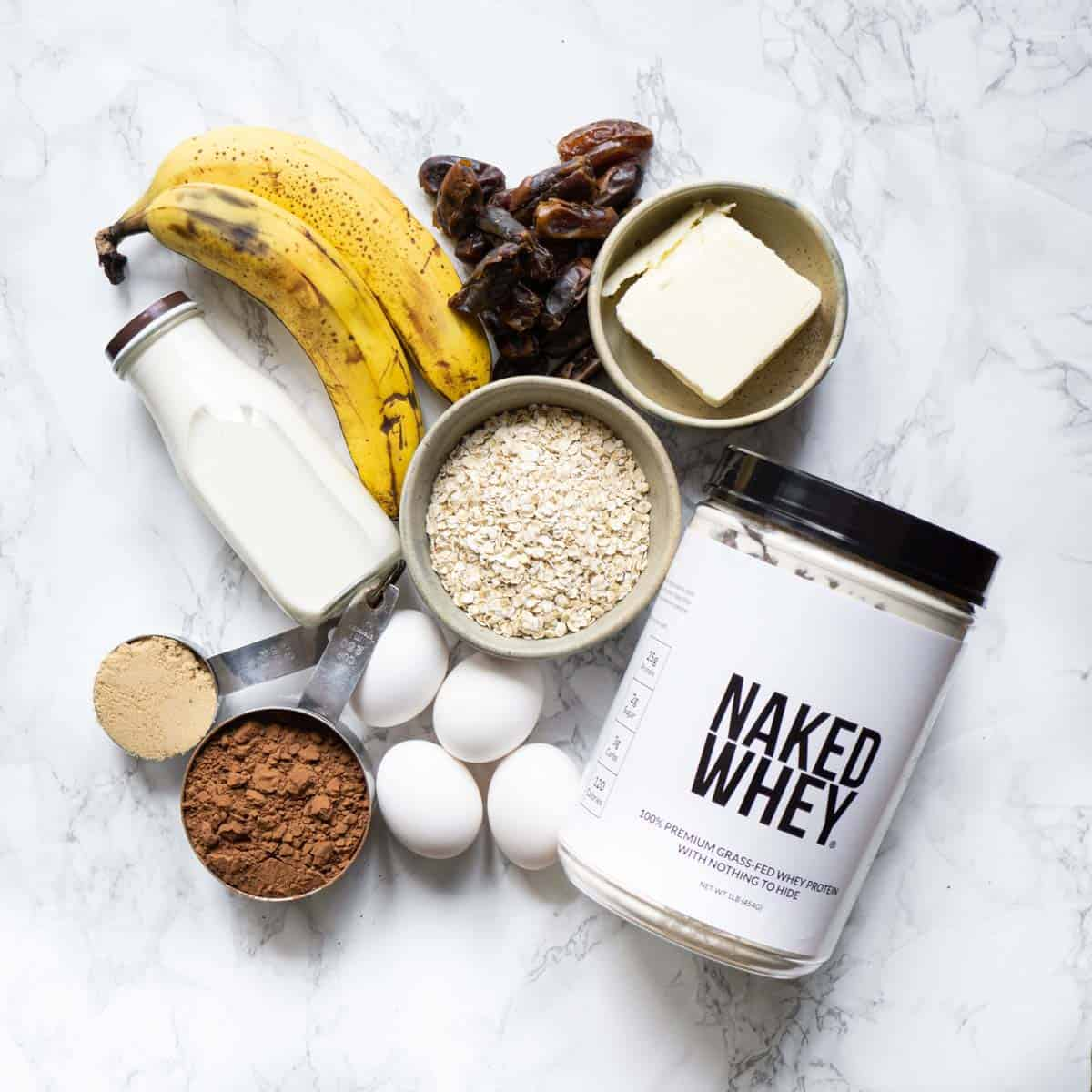 ingredients needed to make protein brownies, including naked whey protein powder, cocoa, eggs, oats, butter, dates, bananas, milk, and brown sugar