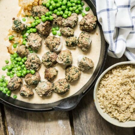swedish meatballs in a cast iron pan with a bowl of rice and peas