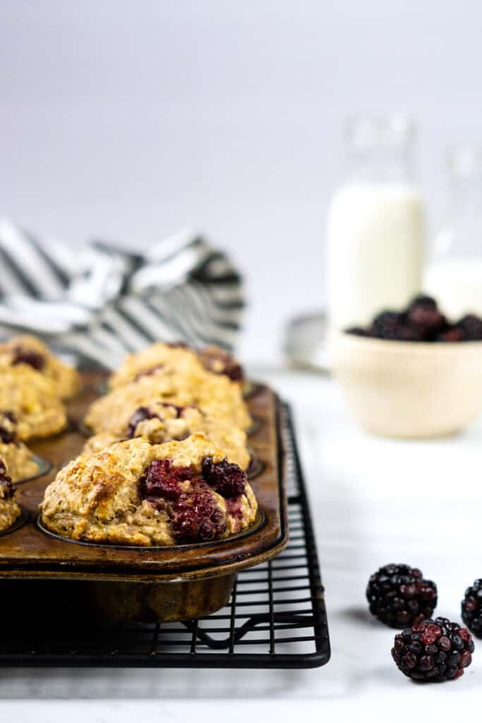 Blackberry oatmeal muffins cooling in a pan on a cooling rack beside a bowl of fresh blackberries and a small glass jug of milk.