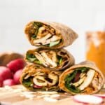 a side view of halloumi wraps with spinach, radishes, and romesco sauce