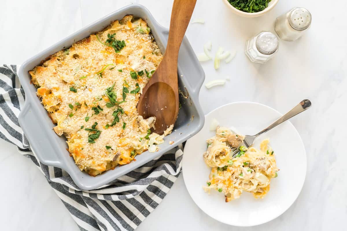Baking dish with creamy tuna noodle casserole with a serving spoon that has scooped out a plateful, which is right beside the baking dish.
