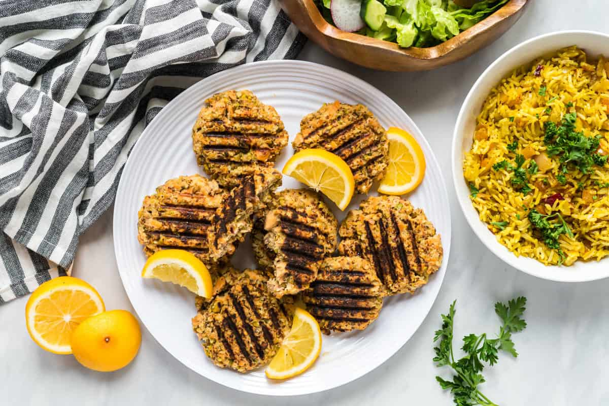 A plate of pistachio salmon cakes with a salad and a bowl of apricot rice to the side.