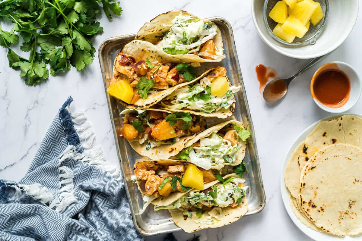 Flatlay view of a sheetpan of pineapple chicken tacos with cilantro slaw with a bowl of pineapple, stack of corn tortillas, and fresh cilantro.