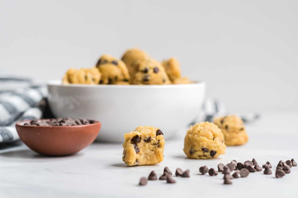 A bowl of edible chocolate chip cookie dough bites with a few beside. One has a bit taken out to show the texture.