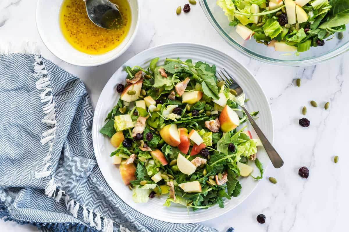 flatlay view of a plat of bacon apple arugula salad with cranberries, pumpkin seeds and a bowl of lemon vinaigrette on the side